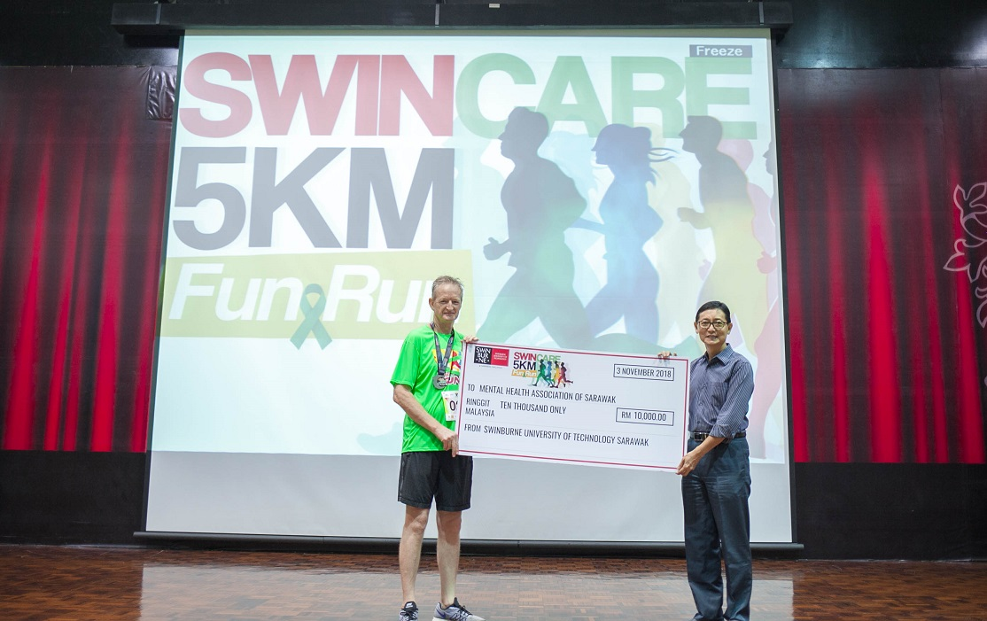 Professor Wilson (left) presenting a mock cheque to Deputy Chairperson of MHAS Kuching Branch Dr Lau Kim Kah at the end of the event.