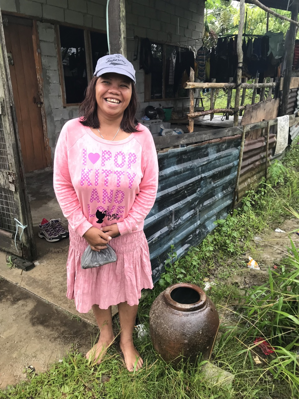 Aida standing next to a small earthenware pot that she uses to store rainwater.