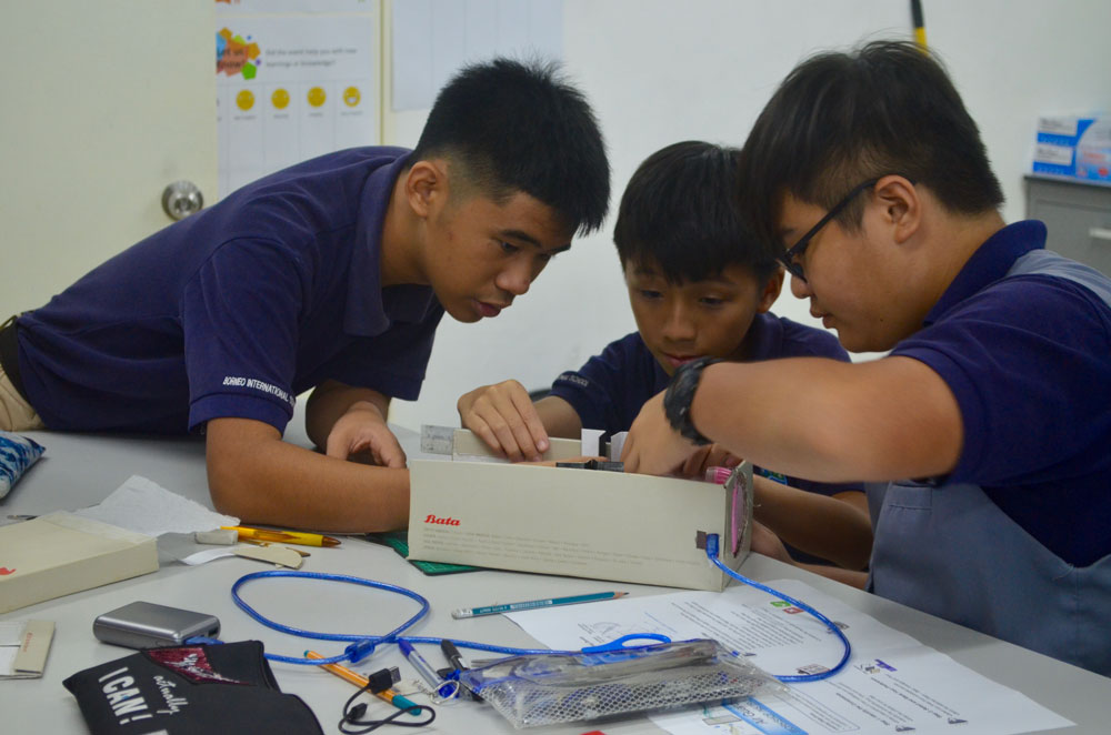 Students working in teams to build their air guard air filters made out of shoeboxes, mini fans, and other materials.