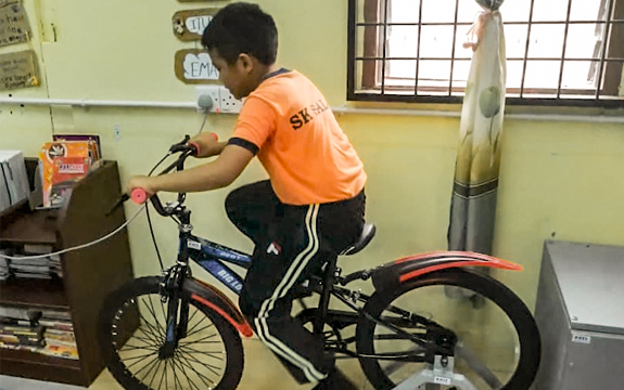 A young student from SK Salak uses pedal power to drive the generator.